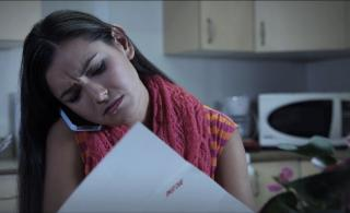 Screenshot of With Child Without Alcohol commercial - a woman on the phone frowning at a paper in her hand.